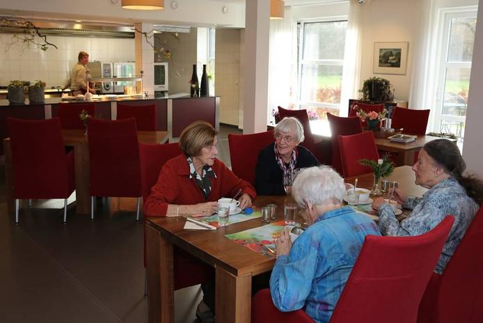 Enkele bewoners van De Nieuwenhof kletsen gezellig in het restaurant.