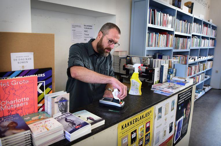 Rogier van boekhandel Steven Sterk in Utrecht maakt de pinautomaat schoon. Beeld Marcel van den Bergh / de Volkskrant