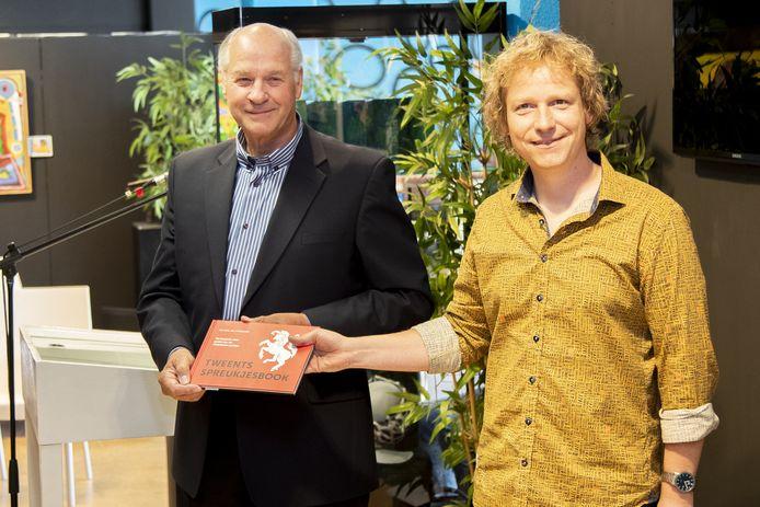 Erik Hütte (l) schenkt het eerste exemplaar van zijn Tweents Spreukenboek aan cabaretier Thijs Kemperink.