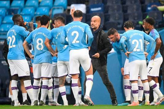 Pep Guardiola (m) instrueert de spelers van Manchester City.