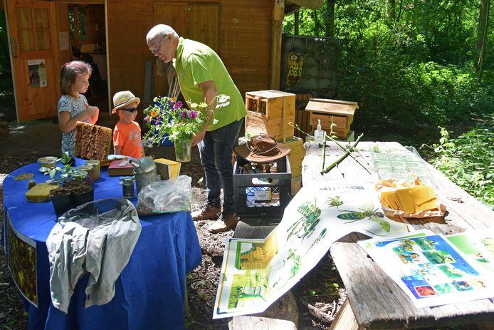 Imker Aad van Hilst legt uit aan Flo en Lex Meyers uit dat bijen stuifmeel van bloemen nodig hebben. In de hoge kist achter Aad bevinden zich zo'n 15.000 bijen.