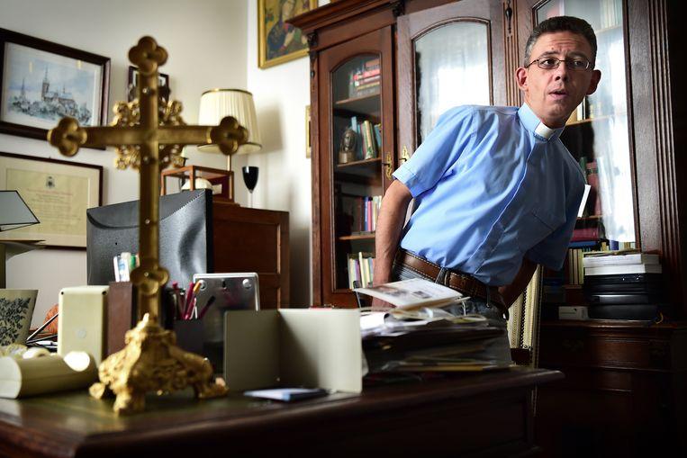 David van Dijk op zijn werkkamer in de parochie, waar hij volgens critici 'te veel spullen' zou hebben.  Beeld Marcel van den Bergh / de Volkskrant