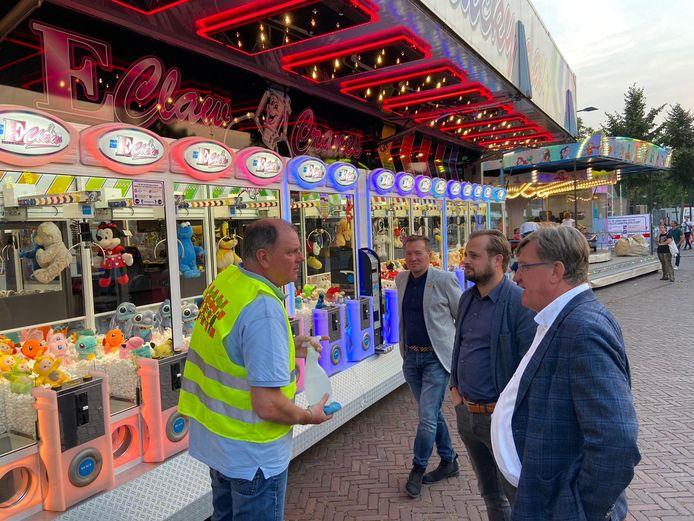 Burgemeester Henk Hellegers, wethouder Gijs van Heeswijk en kermiscoördinator Pascal Donkers in gesprek met een kermisexploitant