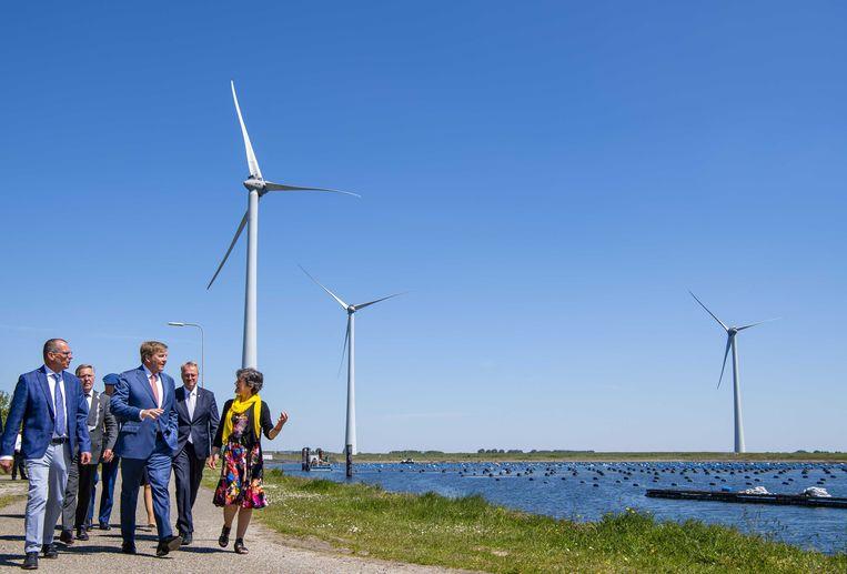 Koning Willem-Alexander wandelt met Teus Baars van Zeeuwind (links) en Monique Sweep van Deltawind (rechts) door Windpark Krammer in Zeeland. Beeld ANP