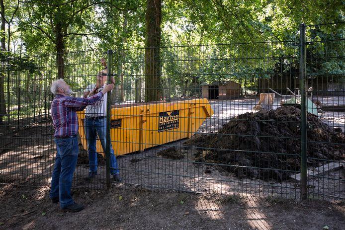 Adriaan Doets (rechts) en Herman Heijts monteren het hek weer nadat er een container is binnengebracht. Ernaast ligt een hoop stalmest van de damherten die daarin wordt afgevoerd.