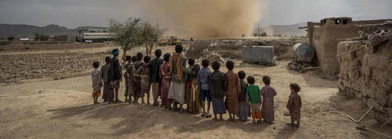 Kinderen kijken naar een kleine tornado in de woestijn in Jemen, 80 kilometer ten noorden van de hoofdstad Sanaa. Beeld Giles Clarke / Getty