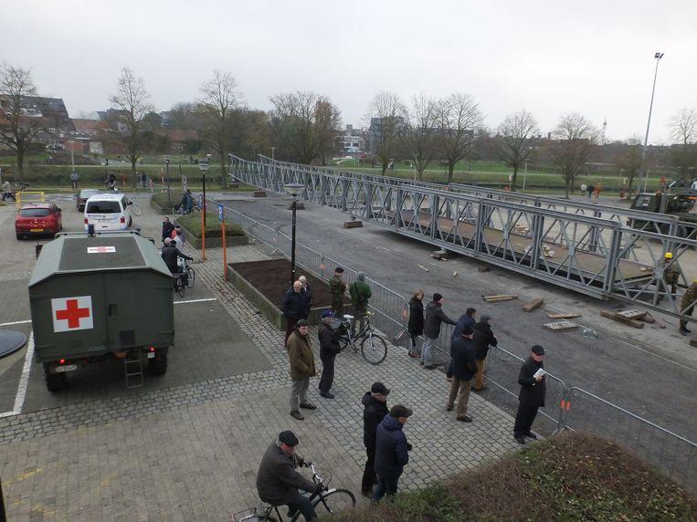 Op de parking van de Brielpoort is men aan het werken aan een noodbrug die donderdag over de Leie wordt geschoven.
