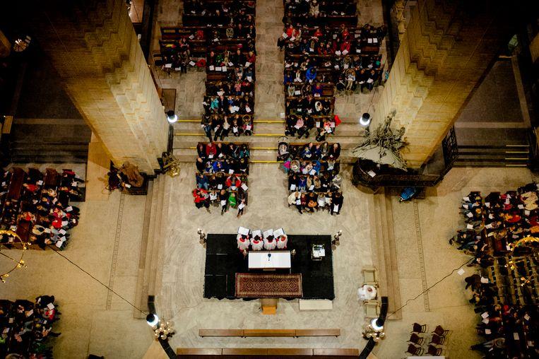 Bezoekers luisteren in 2014 tijdens de kerstviering voor gezinnen met kinderen in de Kathedrale Basiliek Sint Bavo, een viering van woord en gebed rondom het kerstverhaal.  Beeld ANP