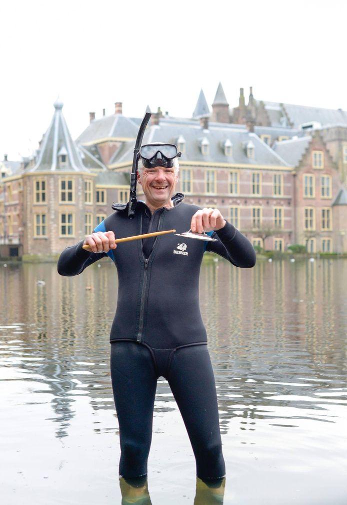 Lid van de Jostiband Erwin Bloem (57) poseert in de Hofvijver van Den Haag met een pannendeksel en een drumstick.