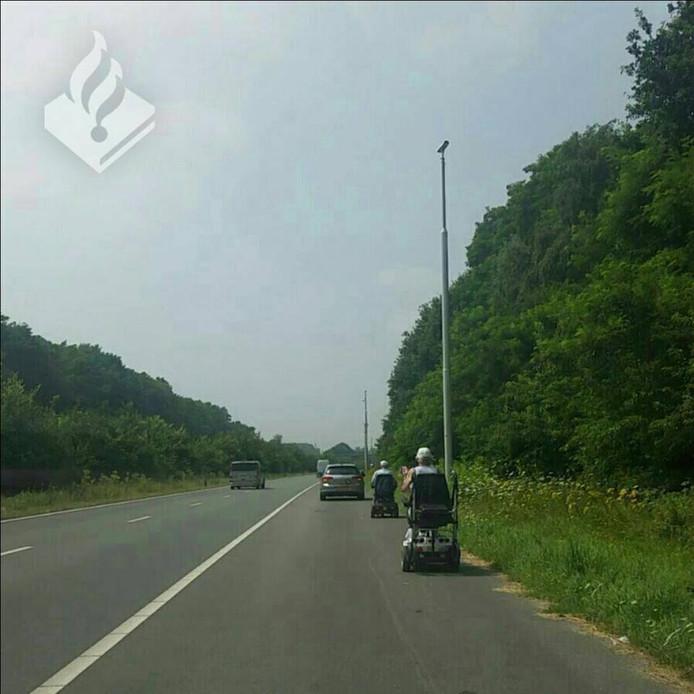 Het echtpaar op de vluchtstrook in hun scootmobiel.