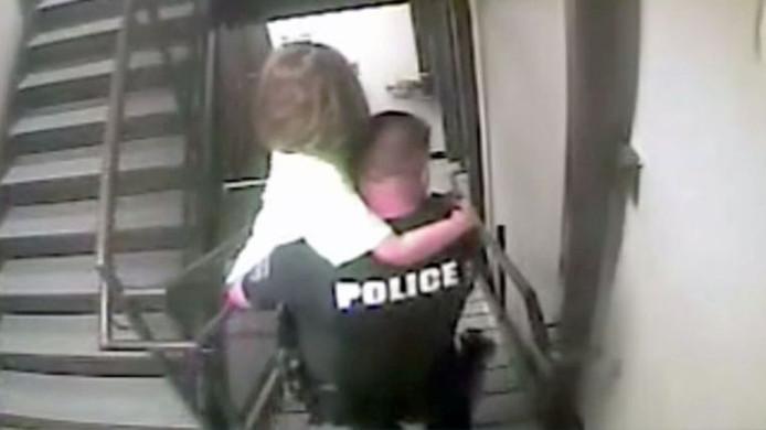 Un policier quitte l'hôtel avec la fillette dans les bras.