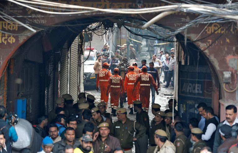 Ambulances zijn ter plekke terwijl politie en brandweer aan het werk zijn bij een brand in fabriek in New Delhi, waarbij tenminste 40 arbeiders omkwamen.