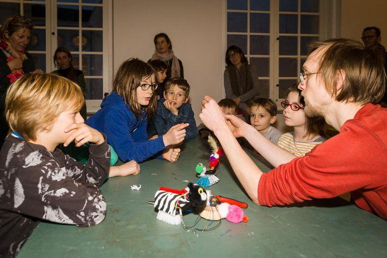 De kinderen leren hoe ze een robot moeten maken van een afwasborstel.