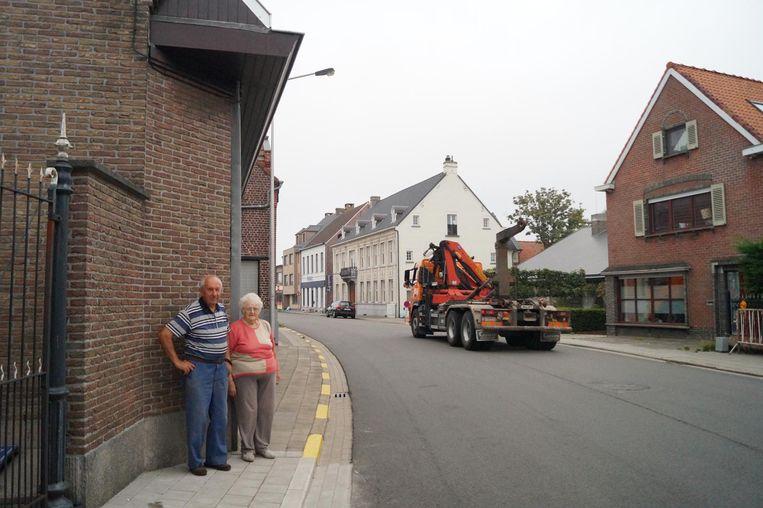 André en Norma onder hun dakgoot, die zodanig dicht bij de weg ligt dat truckers er vaak tegenaan rijden.