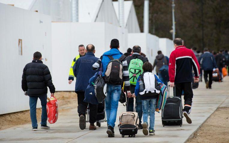 Vluchtelingen vertrekken van een tijdelijke noodopvang in Nederland. Beeld anp