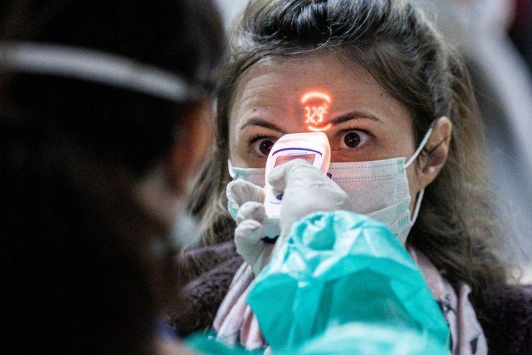 De temperatuur van een vrouw wordt gemeten op de luchthaven van Debrecen, Hongarije. Beeld Bloomberg via Getty Images