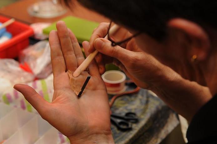 Een lid van de Lotus wrijft het brooddeeg uit over haar hand, die zogenaamd door een boor is doorkliefd. foto: Ed van Alem