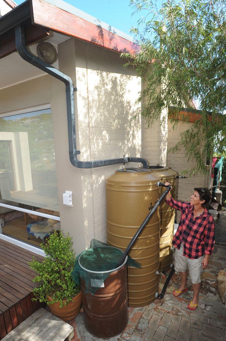 Michele Harvey laat het systeem zien waarmee de inwoners van Scarborough regenwater opvangen. Beeld Brenton Geach