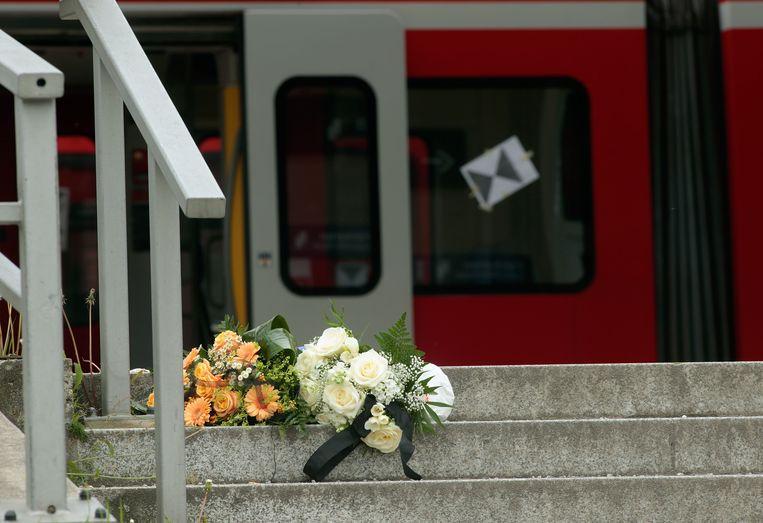 Bloemen ter nagedachtenis aan de slachtoffers van de steekpartij op de trap voor het station. Beeld getty