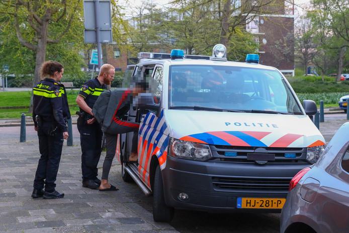 De politie arresteert een van de jonge verdachten.