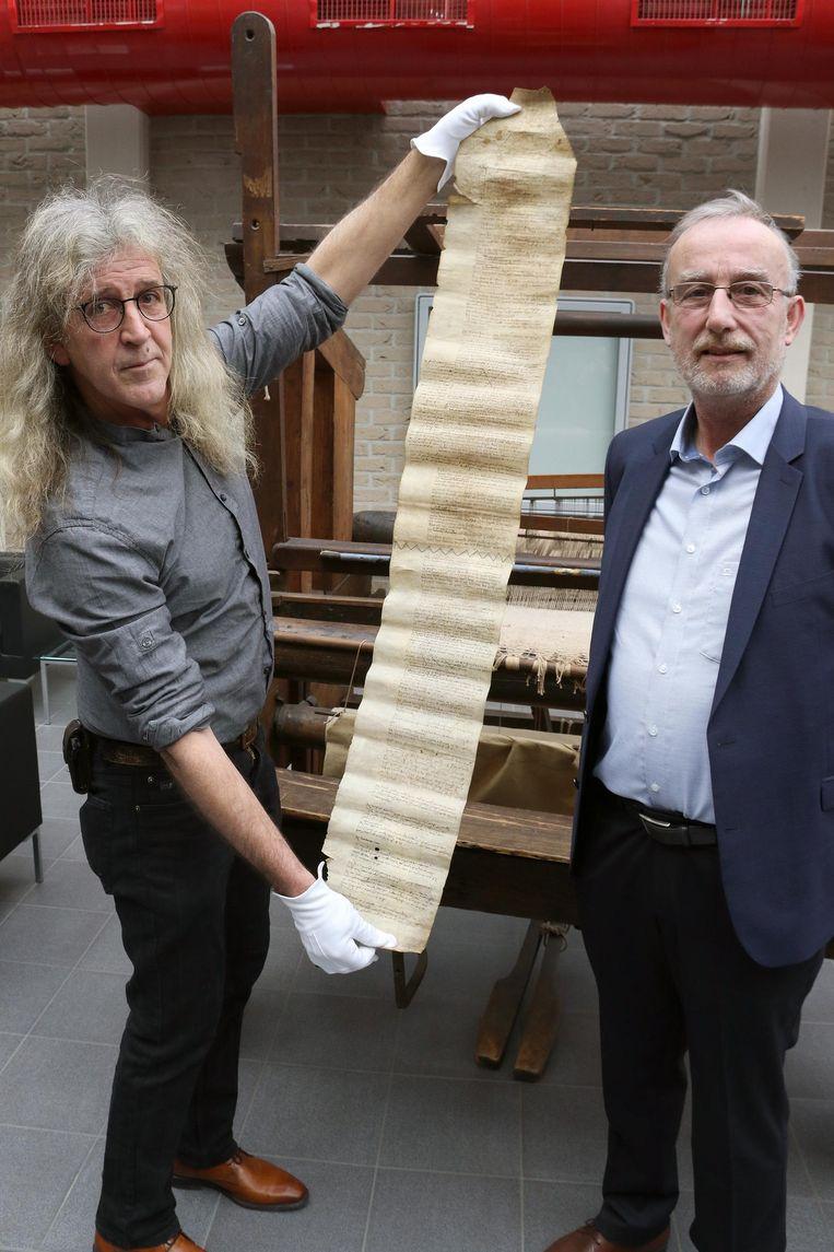 Jo Lommelen van de Kamer voor Heemkunde en Michel Oosterbosch van het Rijksarchief tonen het document. De witte handschoenen moeten vermijden dat het perkament beschadigd raakt.