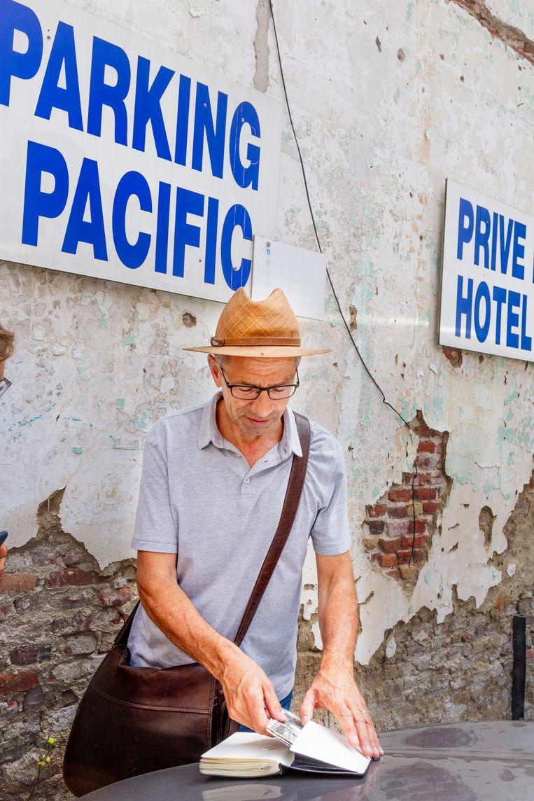 Koen Peeters stopt stukjes Oostendes groen in zijn notitieboekje, die hij van een oude muur heeft geschraapt.  Beeld null
