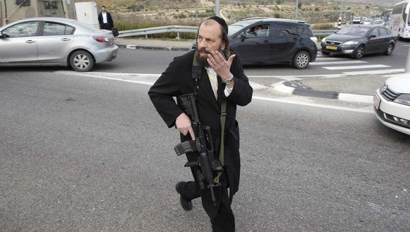 Een Israëlische kolonist met een aanvalsgeweer nabij de plaats delict.