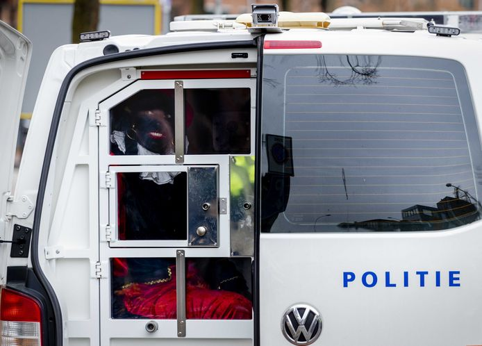 Leden van Pegida verkleed als Zwarte Piet worden aangehouden in Apeldoorn tijdens de intocht van Sinterklaas.