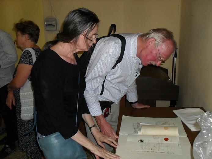 Jacques en Alda van de Ven bekijken de overlijdensakte van Giovanni Castione. Deze akte ligt in Premosello en heeft een stempel van Oirschot.