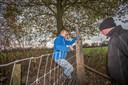 Henk van den Berg (in blauwe jas) plaatst samen met vrijwilligers van stichting Wolf-Fencing wolfwerende hekken om zijn schapen te beschermen. De hobbyboer uit Ruurlo is de eerste boer in de Achterhoek die dit doet.