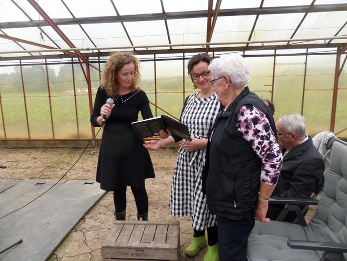 Antje van de Wetering (rechts) krijgt het boek van haar dochter Tini (links en Renata Rakolcai.