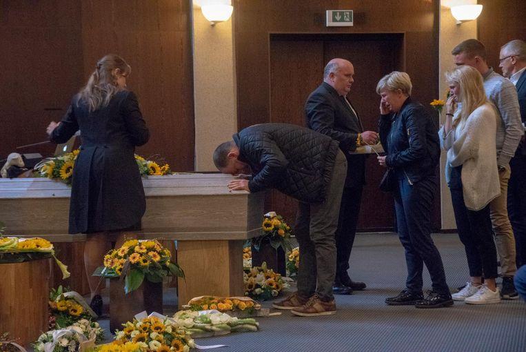 Zijn ouders en zus Charlotte nemen afscheid aan de met bloemen omgeven kist.