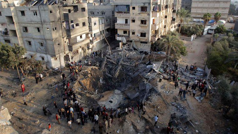 Palestijnen verzamelen zich rond een gebombardeerd huis in de Gazastrook Beeld REUTERS