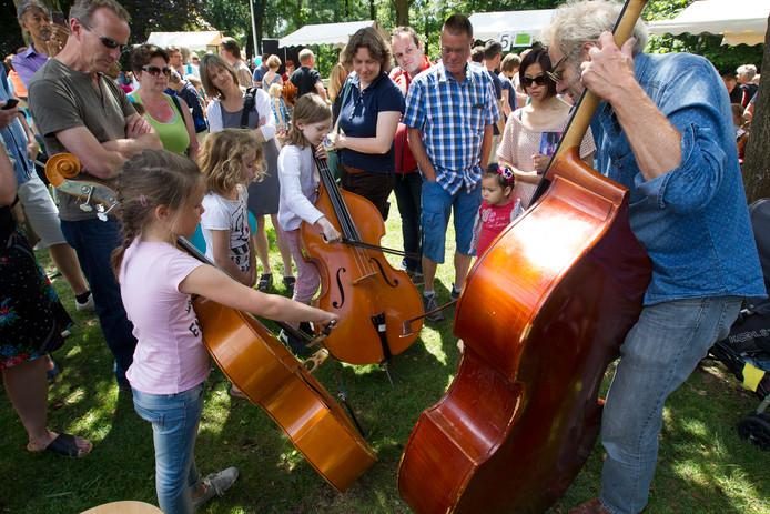 Kinderen maken kennis met diverse muziekinstrumenten in de kinderspeeltuin tijdens Muziek op de Dommel.
