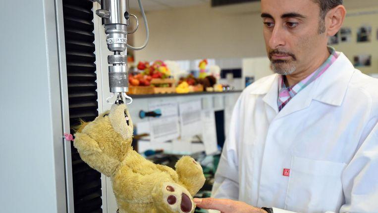 Een teddybeer wordt getest in een laboratorium in Marseille, als onderdeel van een testcampagne voor speelgoedveiligheid. Beeld afp