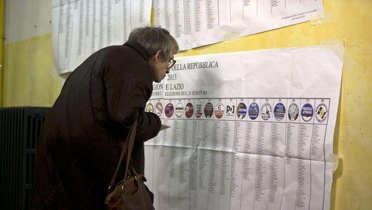 Een vrouw verdiept zich in de kieslijsten van de Italiaanse parlementsverkiezingen Beeld epa