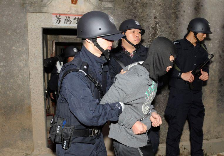 De Chinese politie arresteert een drugsverdachte in het dorp Lufeng. Beeld REUTERS