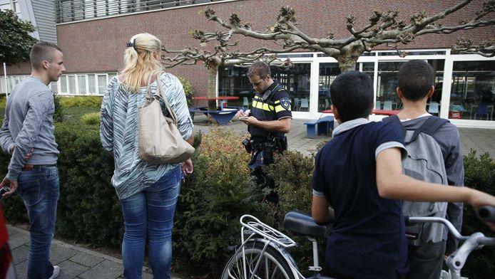 Een lid van de politie doet onderzoek bij het Corbulo College.