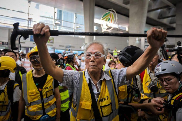 'Opa Wong' gebruikt zijn wandelstok om politie en demonstranten in Hongkong te scheiden. De 85-jarige man is geregeld aanwezig bij protesten tegen de overheid. Beeld AFP