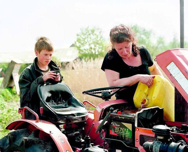 Hannie vult de brandstoftank van de trekker, zoon Daniël kijkt mee. FOTO UIT 'A FALLING HORIZON' Beeld