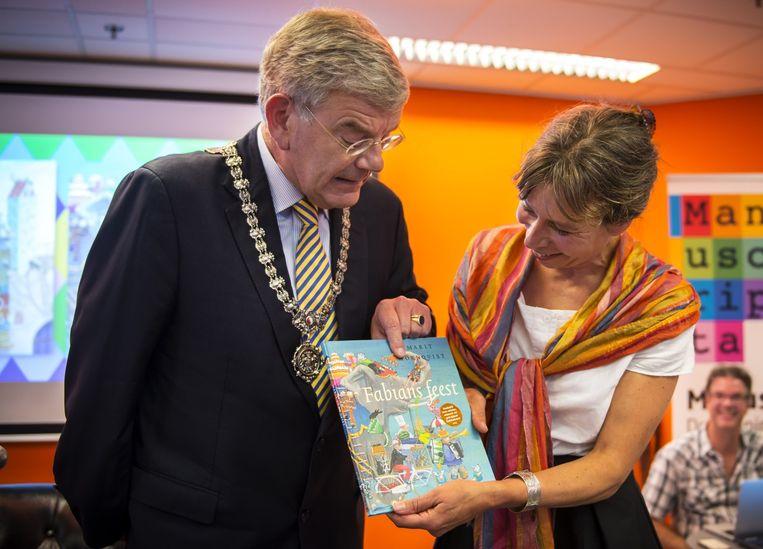 Burgemeester Jan van Zanen van Utrecht, reikt het eerste exemplaar van het prentenboek van de Kinderboekenweek uit aan Marit Tornqvist, bij de opening van het boekenseizoen. Beeld anp