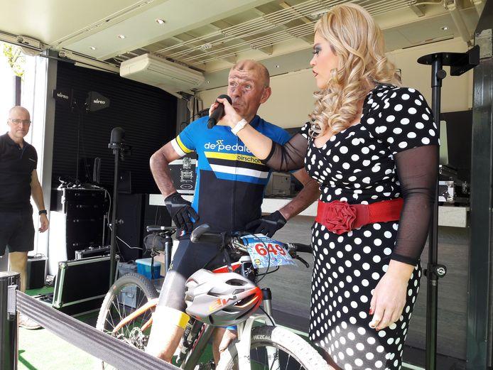 Patty Pitt interviewt Frans Willems, die als eerste van 592 deelnemers aan de Vrijthof-Vrijthof Bike-Challenge over de meet in Hilvarenbeek kwam