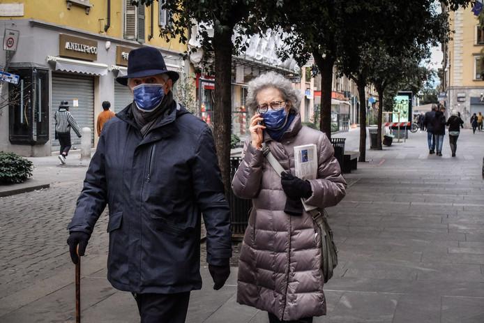 Wandelaars in Milaan, waar in de omgeving veel besmettingen met het coronavirus zijn