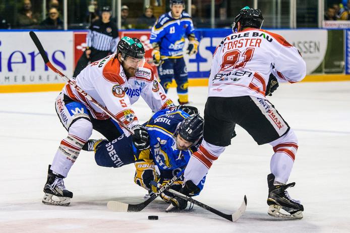 Peter van Biezen wordt door twee spelers van Landshut tegen het ijs gedrukt.