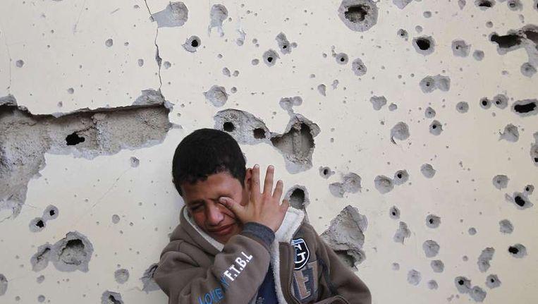 Het 11-jarige Palestijnse jongetje Fares Sadallah staat voor zijn beschadigde huis in Beit Lahia. Beeld afp