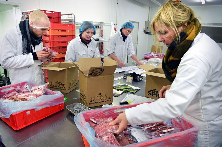 In een koelcel in Haaksbergen worden de pakketten van SamenEenVarkenKopen ingepakt. Op de voorgrond (met geelzwarte sjaal) initiatiefnemer Kirsten Marsman. Beeld Marcel van den Bergh