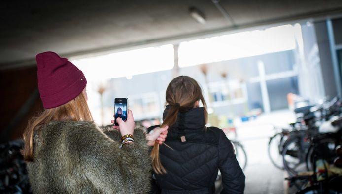 Een scholiere pest een schoolgenootje en filmt dit met een smartphone.