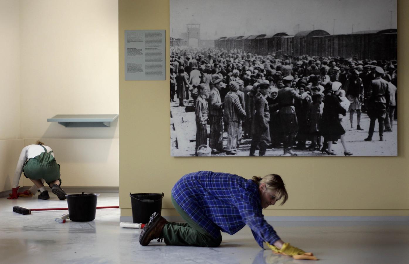 Foto ter illustratie. Schoonmaaksters dweilen de vloer van Museum Auschwitsch met op de achtergrond een foto van de aankomst van een transport met uit Nederland afkomstige Joden bij vernietigingskamp Auschwitz-Birkenau.