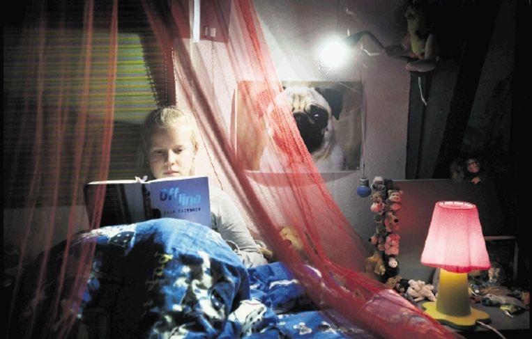 Renske (12) leest het liefst in bed. Bijvoorbeeld in 'Off line' van Caja Cazemier. (FOTO WERRY CRONE) Beeld