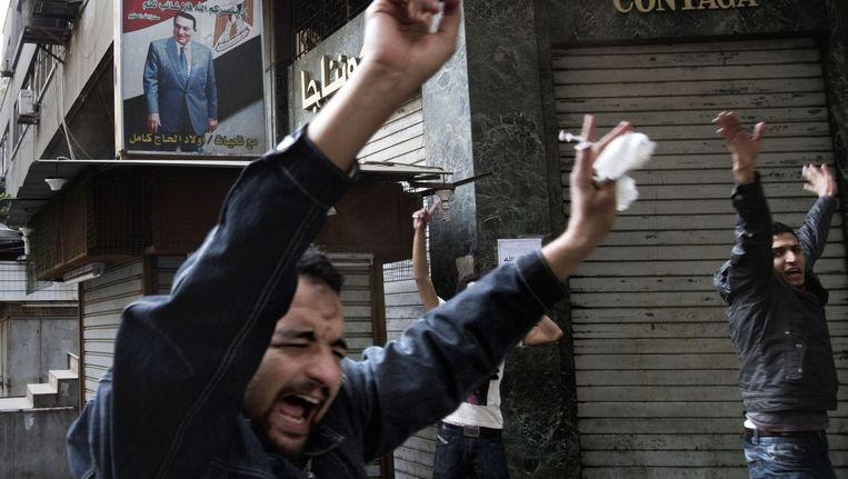 Egyptische demonstranten schreeuwen leuzen naar een poster van hun president Hosni Mubarak, januari 2011. Beeld anp